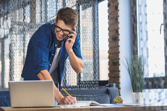 Freelancer talking with client by phone Stock Photography