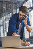 Freelancer talking on his smartphone in front of a laptop. I am listening, freelancer solving a problem by smartphone in front of laptop Royalty Free Stock Images