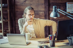Freelancer thoughtfully looking in computer. Male thinking holdig his hand close to chin Stock Images