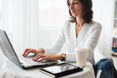 Freelancer using notebook, woman working on laptop Stock Photography