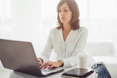 Freelancer using notebook, woman working on laptop computer typing the keyboard at home royalty free stock images