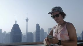 Freelancer using smartphone on modern city background.