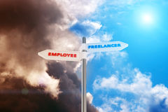 Freelancer vs Employee. Road sign Freelancer - Employee against a contrast sky Royalty Free Stock Image