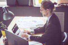 Freelancer w czarnym garniturze pracuje z laptopem Fotografia Stock