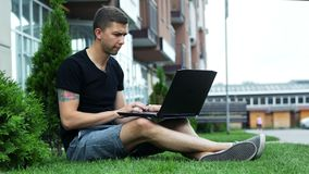 Freelancer work on laptop in the open air while sitting on grass stock video footage