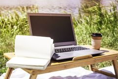 Freelance outdoor summer work concept. Freelancer work in summer on a picnic in nature. Laptop on a bamboo table on a coverlet by the river Royalty Free Stock Image