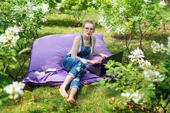 Freelancer working in the garden. Writing, surfing in the internet. Young woman relaxing and having fun in park area. Distance edu. Cation, freelance concept Stock Photo