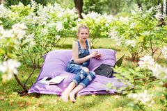 Freelancer working in the garden. Writing, surfing in the internet. Young woman relaxing and having fun in park area. Distance edu. Cation, freelance concept Royalty Free Stock Photo