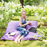 Freelancer working in the garden. Writing, surfing in the internet. Young woman relaxing and having fun in park area. Distance edu Stock Photo