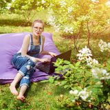 Freelancer working in the garden. Writing, surfing in the internet. Young woman relaxing and having fun in park area. Distance edu. Cation, freelance concept Royalty Free Stock Photos