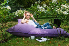 Freelancer working in the garden. Writing, surfing in the internet. Young woman relaxing and having fun in park area. Distance edu Royalty Free Stock Image