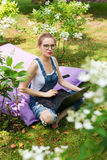 Freelancer working in the garden. Writing, surfing in the internet. Young woman relaxing and having fun in park area. Distance edu Royalty Free Stock Photo