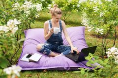 Freelancer working in the garden. Writing, surfing in the internet. Young woman relaxing and having fun in park area drinking coff. Ee. Distance education Royalty Free Stock Photo