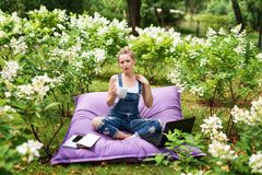 Freelancer working in the garden. Writing, surfing in the internet. Young woman relaxing and having fun in park area drinking coff. Ee. Distance education Royalty Free Stock Image