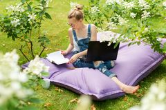 Freelancer working in the garden. Writing, surfing in the internet. Young woman relaxing and having fun in park area drinking coff. Ee. Distance education Royalty Free Stock Photos