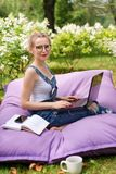 Freelancer working in the garden. Writing, surfing in the internet. Young woman relaxing and having fun in park area drinking coff. Ee. Distance education Stock Photos