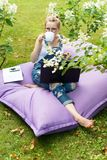 Freelancer working in the garden. Writing, surfing in the internet. Young woman relaxing and having fun in park area drinking coff. Ee. Distance education Stock Photo