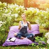 Freelancer working in the garden. Writing, surfing in the internet. Young woman relaxing and having fun in park area drinking coff. Ee. Distance education Royalty Free Stock Photography