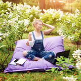 Freelancer working in the garden. Writing, surfing in the internet. Young woman relaxing and having fun in park area drinking coff Royalty Free Stock Photography