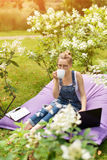Freelancer working in the garden. Writing, surfing in the internet. Young woman relaxing and having fun in park area drinking coff Royalty Free Stock Photos