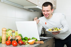 Freelancer working and holding vegies. Satisfied male freelancer working with laptop holding vegies in the kitchen Royalty Free Stock Image