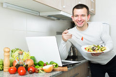 Freelancer working and holding vegies. Satisfied positive freelancer working with laptop holding vegies in the kitchen Stock Photography