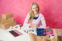 Freelancer working from home. Woman making jewellery and selling merchandise online royalty free stock images