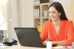 Freelancer working with a laptop. Beautiful freelancer working with a laptop in a desk at home room or office Royalty Free Stock Photography