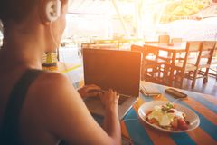 Freelancer working at laptop in caffe. Intentional sun glare royalty free stock image