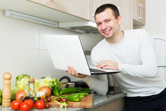 Freelancer working with laptop. Happy young male freelancer working with laptop from home Royalty Free Stock Photography