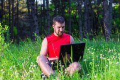 Freelancer working on a laptop outdoors. Workaholic, work on vacation Stock Images