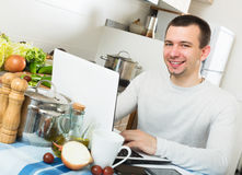 Freelancer working with laptop. Positive young male freelancer working with laptop from home Royalty Free Stock Photo