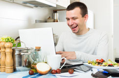 Freelancer working with laptop. Satisfied attractive male freelancer working with laptop from home Stock Photo