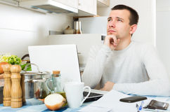 Freelancer working with laptop. Serious male freelancer working with laptop from home Stock Photo
