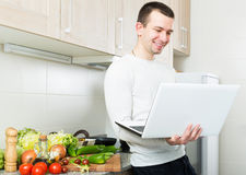 Freelancer working with laptop. Smiling young male freelancer working with laptop from home Royalty Free Stock Photos