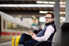 Freelancer working with a laptop in a train station while is waiting for transport Stock Photo