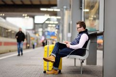 Freelancer working with a laptop in a train station while is waiting for transport. Handsome middle age man on on railway station platform stock photo