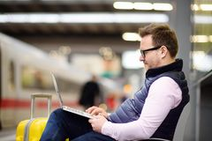 Freelancer working with a laptop in a train station while is waiting for transport Stock Image