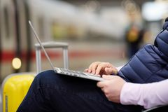 Freelancer working with a laptop in a train station while is waiting for transport royalty free stock photography
