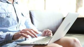 Freelancer Working on Project on Laptop. Young Man, Businessman, entrepreneur, creative designer, freelancer sitting on Couch and working on his project on stock footage