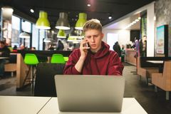 Freelancer works on a laptop in a cafe and calls the phone. Business young man sitting with a laptop in a fast food cafe stock images
