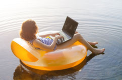 Freelancer works on a laptop sitting in an inflatable ring in th. E water, free space. Business woman working and relaxing on the beach stock photography