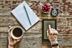Freelancer works with a tablet computer at home at the table, next to it there is an open notepad and a pencil, a clock. In his ha. Nd a cup of coffee. The royalty free stock photo