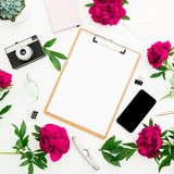 Freelancer workspace with clipboard, dairy, peony flowers, retro camera and smartphone on white background. Flat lay, top view. Be. Auty blog concept Stock Images