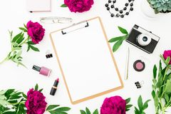 Freelancer workspace with clipboard, dairy, peony flowers and retro camera on white background. Flat lay, top view. Beauty blog co. Ncept Stock Photos