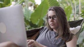 Freelancerarbete Kvinnatyp på bärbara datorn, medan sitta på hängmattan arkivfilmer