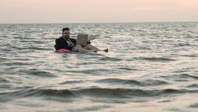 Freelancerbad i det öppna havet på barns uppblåsbara cirkel och arbeten med en bärbar dator på hans knä stock video