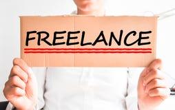 Freelancerbegrepp med kvinnan som rymmer en papp Arkivfoto