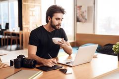 Freelanceren uppsökte mannen som dricker kaffe på bärbar datorsammanträde på skrivbordet Arkivfoton