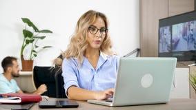 Freelancerkvinna som arbetar på bärbara datorn, medan hennes pojkvän gör mycket oväsen i bakgrunden arkivfilmer